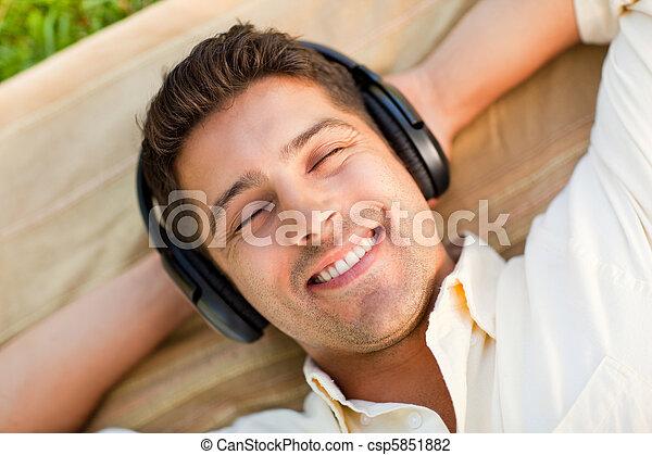 Joven escuchando música en el parque - csp5851882