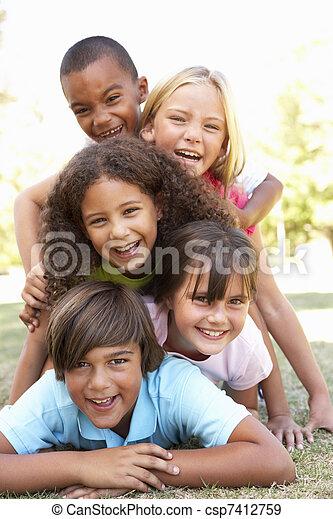 Un grupo de niños amontonados en el parque - csp7412759