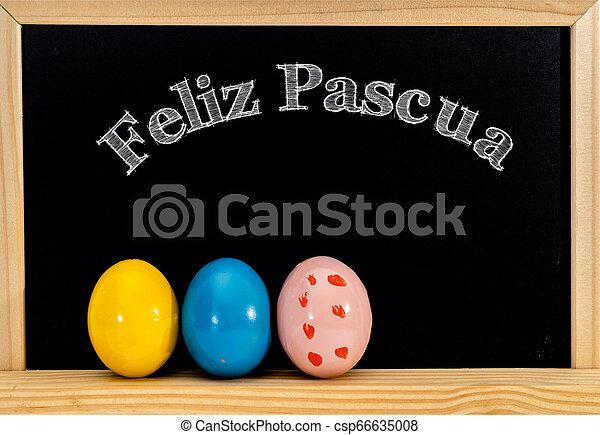 Encuadre de Pascua con huevos pintados y pizarra. Feliz Pascua con tiza blanca. Feliz Pascua en español: feliz pascua - csp66635008
