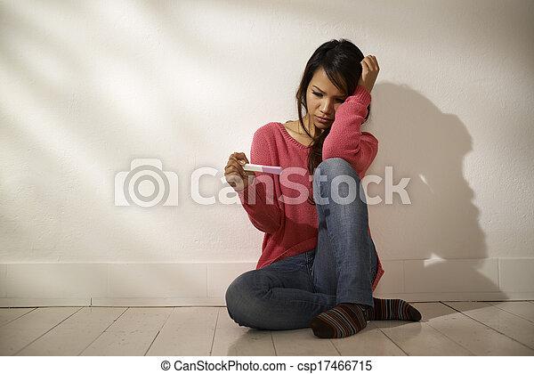 Chica asiática triste mirando la prueba de embarazo sentada en el suelo - csp17466715