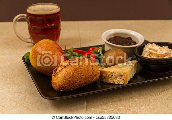Ploughmans almuerza con queso stilton y media pinta de cerveza inglesa. - csp55325633