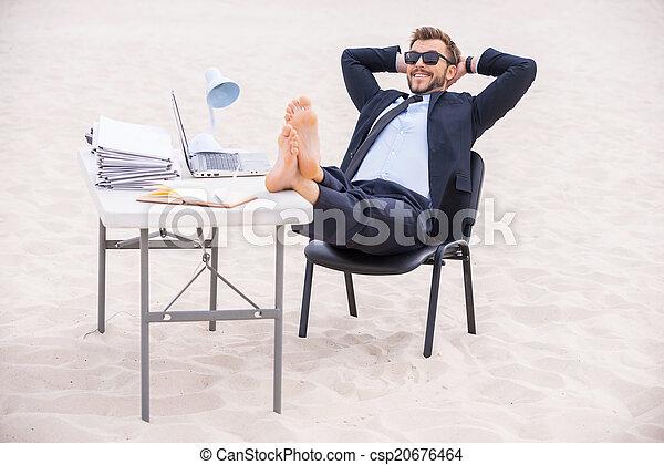 Listo para las vacaciones. Un joven apuesto con ropa formal y gafas de sol sosteniendo sus manos detrás de la cabeza y sosteniendo sus pies sobre la mesa parado sobre la arena - csp20676464