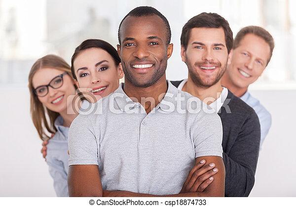 Equipo de negocios confiado. Un joven africano alegre con brazos cruzados y sonriendo mientras un grupo de gente detrás de él en fila y mirando a la cámara - csp18874733