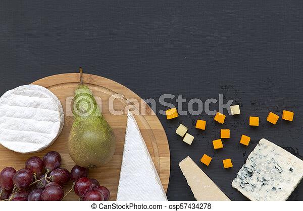 Queso degustador con frutas en fondo oscuro. Comida romántica. Copia espacio. Planta. Desde arriba, desde arriba. - csp57434278