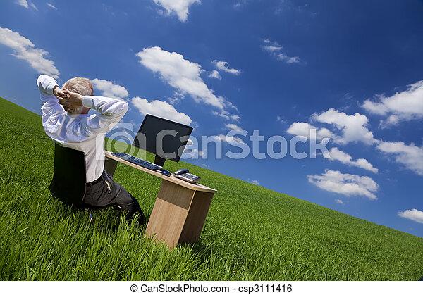 El hombre se relaja en la oficina en un campo verde - csp3111416
