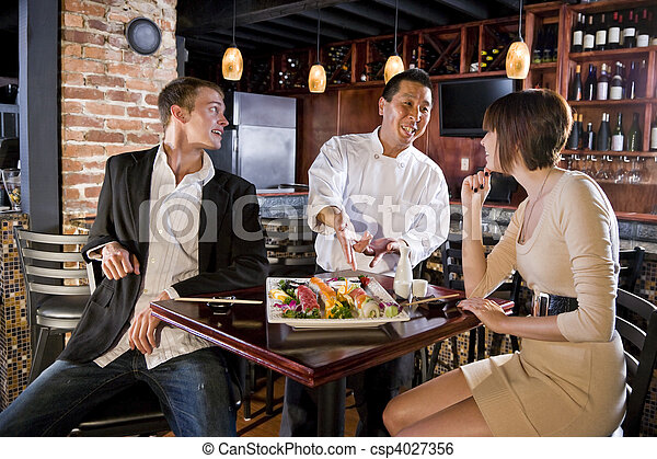 Restaurante japonés, chef sirviendo clientes - csp4027356