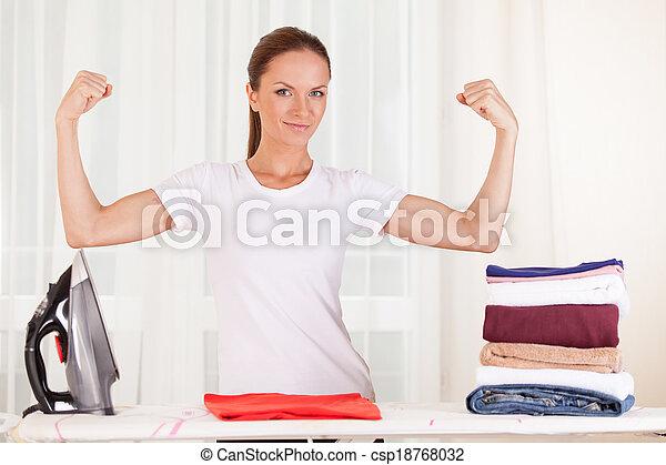 Retrato de ama de casa sonriente planchando ropa. Levantar a ama de casa de pie y mostrar músculos - csp18768032