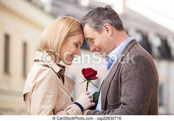 Retrato de dos personas sosteniendo rosa y sonriendo. Hombre adulto dando flores rojas a mujer rubia afuera - csp22630716