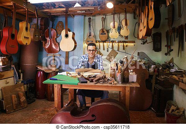 Retrato de feliz artesano lute creador en la tienda de guitarras sonriendo a la cámara - csp35611718