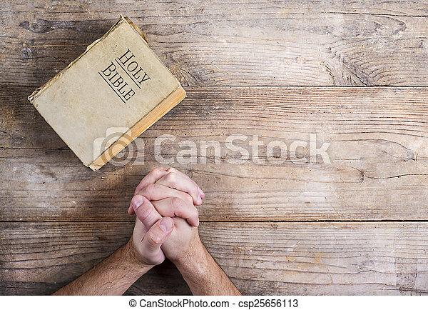 Biblia y manos de oración - csp25656113