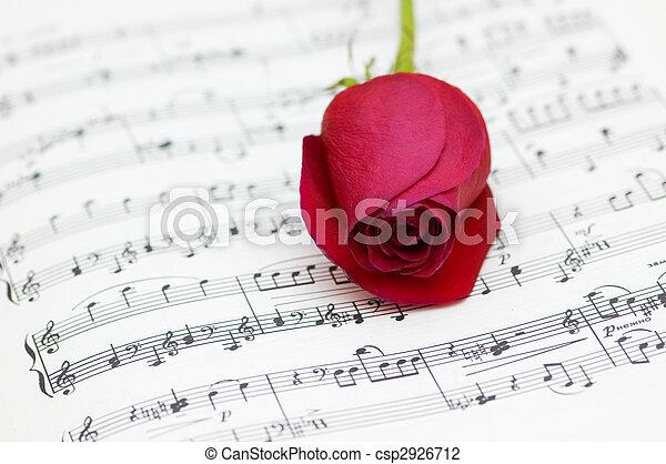 Una rosa roja en la página de notas musicales - csp2926712