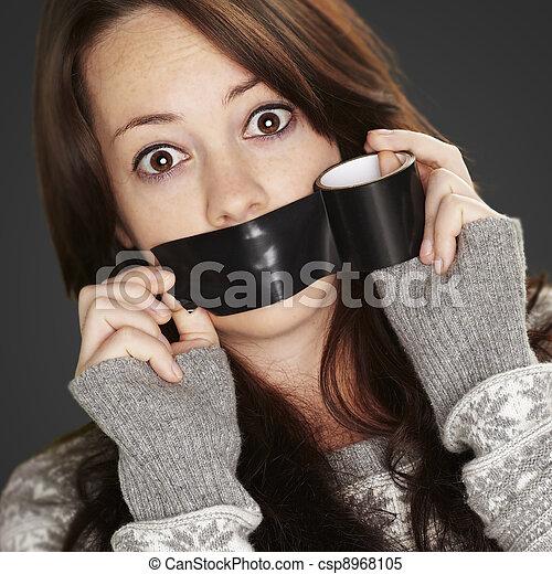 Retrato de chica asustada siendo silenciada por sí misma sobre un bac negro - csp8968105