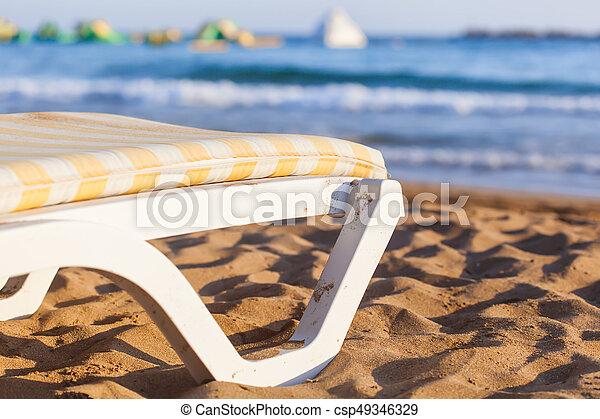 Silla de cubierta en playa arenosa de mar azul - csp49346329
