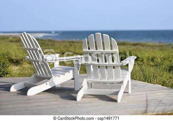 sillas Adirondack en cubierta mirando hacia la playa en la isla calva, Carolina del Norte. - csp1491771