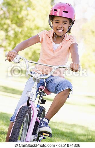 Una joven en bicicleta al aire libre sonriendo - csp1874326
