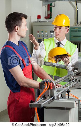 Inspector controlando la seguridad durante el trabajo en la fábrica - csp21498490