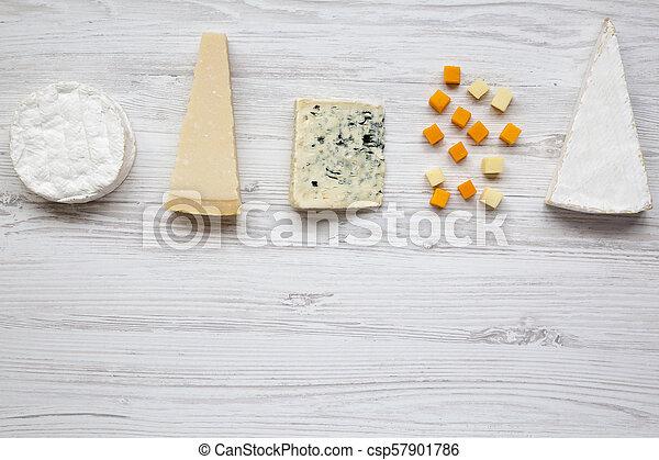Un conjunto de varios quesos en un fondo blanco de madera con espacio de copia. Desde arriba, plano. - csp57901786