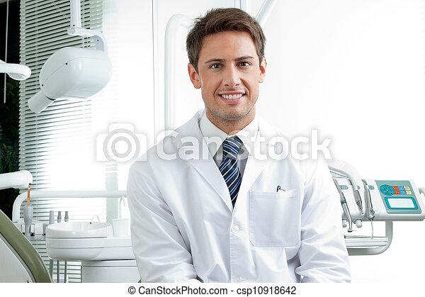 Un dentista masculino feliz en la clínica - csp10918642
