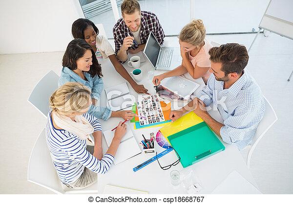 Un equipo de diseño joven revisando sábanas de contacto de fotografía juntos en la oficina creativa - csp18668767