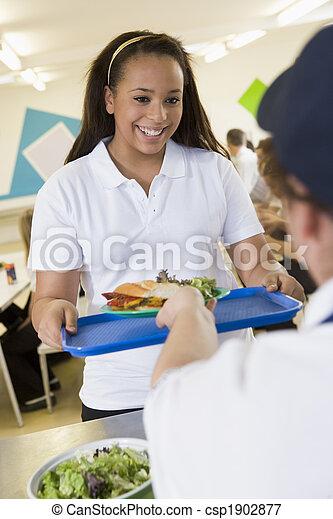 Un estudiante recogiendo el almuerzo de la cafetería de la escuela - csp1902877