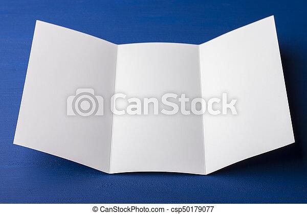 Un folleto en blanco de tres pliegues sobre fondo azul para reemplazar tu diseño o mensaje - csp50179077