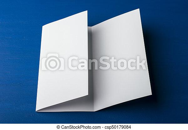 Un folleto en blanco de tres pliegues sobre fondo azul para reemplazar tu diseño o mensaje - csp50179084