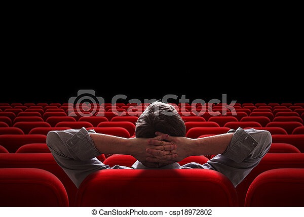Un hombre sentado en el cine vacío o en el auditorio del teatro - csp18972802