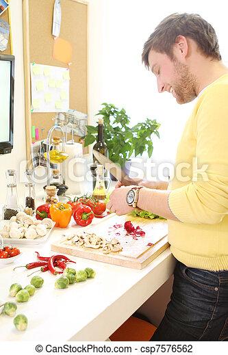 Un joven cocinando comida sana - csp7576562