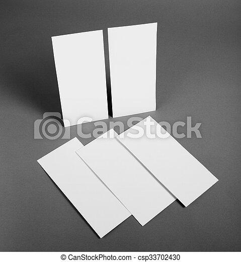 Un póster en blanco sobre un fondo gris para reemplazar tu diseño. - csp33702430
