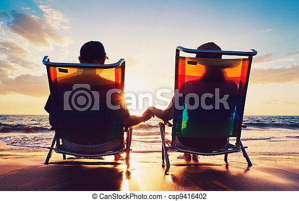 Un par de ancianos sentados en la playa mirando el atardecer - csp9416402