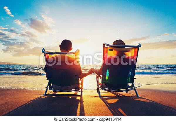 Un par de ancianos sentados en la playa mirando el atardecer - csp9416414