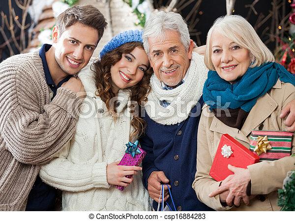 Una familia feliz de pie en la tienda de Navidad - csp16884283