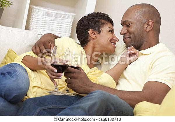 Una feliz pareja americana y una mujer bebiendo vino - csp6132718