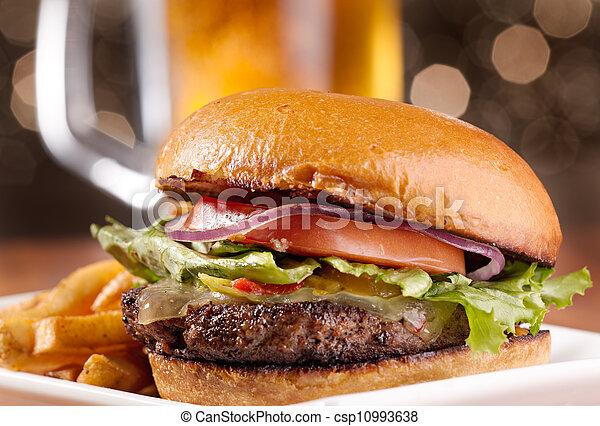 Una hamburguesa con queso con jarra de cerveza en el fondo - csp10993638