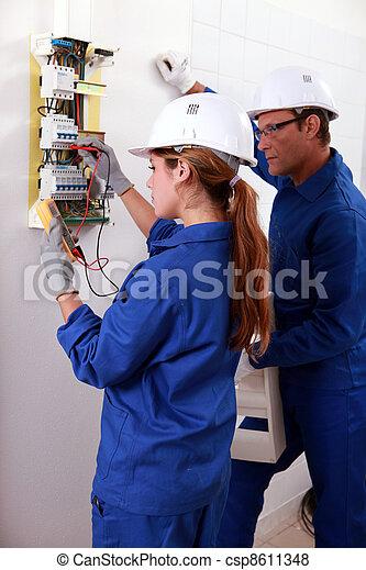 Una joven electricista usando un amómetro para comprobar un contador eléctrico y un hombre mayor vigilándola - csp8611348