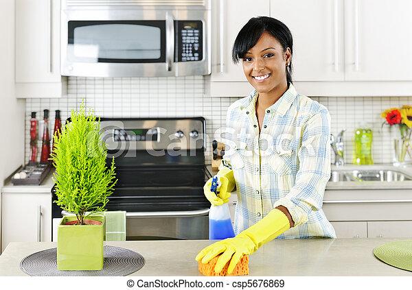 Una joven limpiando la cocina - csp5676869