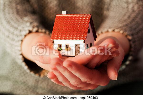 Una mujer sosteniendo una pequeña casa nueva en sus manos. Bienes raíces, hipoteca - csp19894931