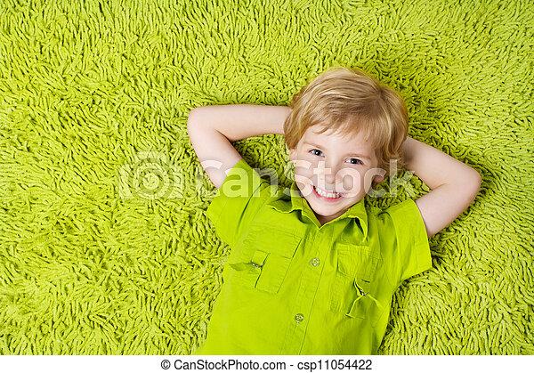 Una niña feliz en el fondo de la alfombra verde. Niño sonriendo y mirando cámara - csp11054422