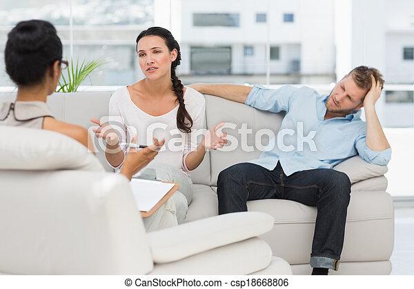 Una pareja enfadada sentada en el sofá hablando con la terapeuta - csp18668806