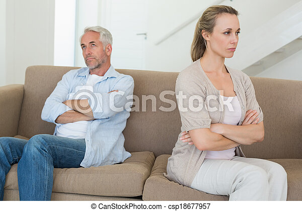 Una pareja enfadada sentada en el sofá sin hablarse - csp18677957