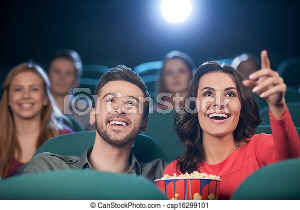 Una pareja feliz en el cine. Una pareja joven y alegre viendo películas en el cine - csp16299101