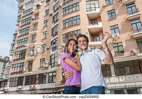 Una pareja frente a una nueva casa con llaves de la puerta. Hombre abrazando a mujer y sosteniendo las llaves del apartamento - csp23009855
