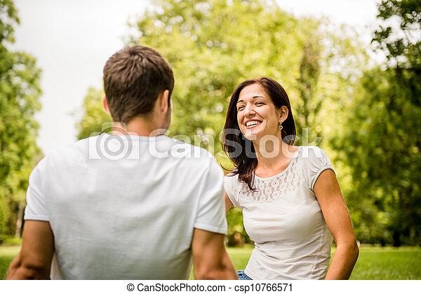 Una pareja joven hablando al aire libre - csp10766571