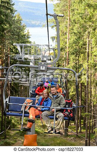 Una pareja joven sentada en el bosque de la silla elevadora - csp18227033