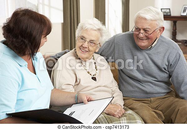 Una pareja mayor en discusión con un visitante en casa - csp7413173