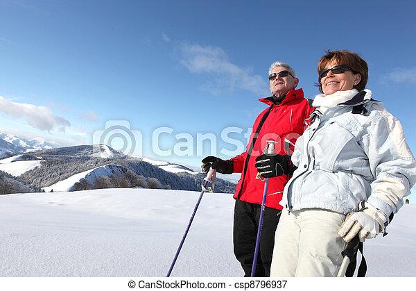 Una pareja mayor esquiando - csp8796937