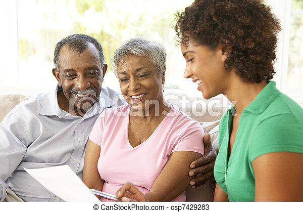 Una pareja mayor hablando con asesor financiero en casa - csp7429283