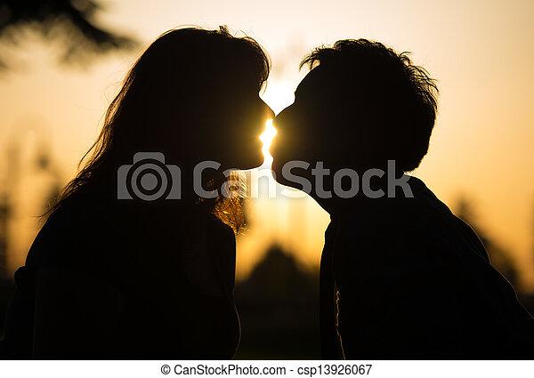 Una pareja romántica besándose al atardecer - csp13926067
