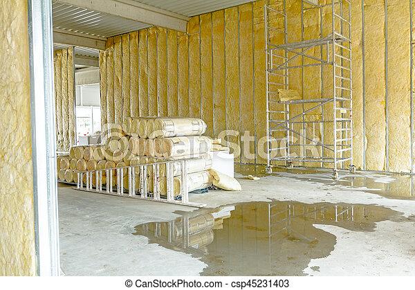 Un paquete de material de aislamiento térmico, lana de roca está envuelta en papel de aluminio. Usó una escalera de madera y un andamio - csp45231403