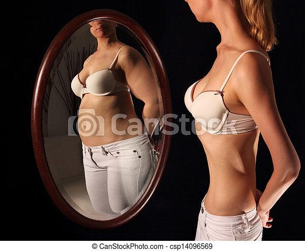 Mujer flaca viéndose gorda en un pajar - csp14096569